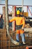 Trabalhador do construtor no trabalho de derramamento concreto Imagens de Stock