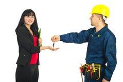Trabalhador do construtor que dá chaves à mulher Fotografia de Stock Royalty Free