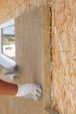 Trabalhador do construtor que instala o material de isolação em uma parede Foto de Stock