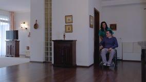 Trabalhador do cuidado com o homem novo na cadeira de rodas em casa video estoque