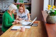 Trabalhador do departamento do bem-estar que indica em artigos do empréstimo à mulher fotografia de stock