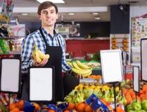 Trabalhador do mantimento que vende frutos sazonais Imagens de Stock Royalty Free
