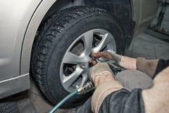 Trabalhador do mecânico de carro que faz a substituição do pneu ou da roda com a chave pneumática na garagem da estação do serviç imagem de stock royalty free
