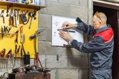 Trabalhador do mecânico que estuda suas instruções foto de stock royalty free