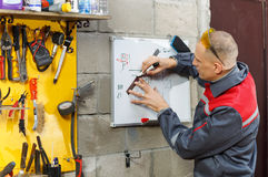 Trabalhador do mecânico que estuda suas instruções Fotos de Stock Royalty Free