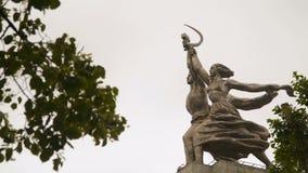 Trabalhador do monumento e mulher Kolkhoz entre os ramos das árvores vídeos de arquivo