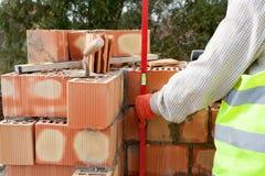 Trabalhador do pedreiro que mede com nível profissional os tijolos sob a construção Imagens de Stock