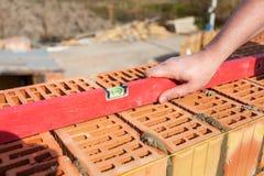 Trabalhador do pedreiro que mede com nível profissional a parede de tijolos nova sob a construção Foto de Stock Royalty Free