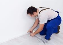 Trabalhador do pintor que prepara a sala - colocando o filme da proteção fotografia de stock royalty free