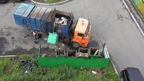Trabalhador do recipiente da carga do caminhão de lixo com lixo em seus escaninhos filme