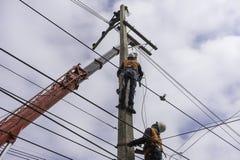 Trabalhador do reparador do lineman do eletricista no trabalho de escalada no polo de poder bonde do cargo Fotografia de Stock