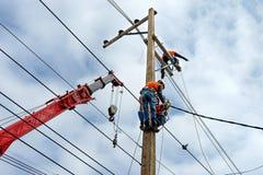 Trabalhador do reparador do lineman do eletricista no trabalho de escalada no polo de poder bonde do cargo Imagens de Stock Royalty Free