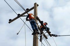 Trabalhador do reparador do lineman do eletricista no trabalho de escalada no polo de poder bonde do cargo Imagem de Stock