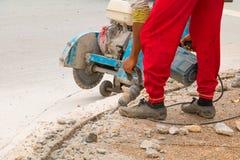 Trabalhador do reparo da perfuração da construção na superfície de estrada com movimento resistente da broca da máquina Fotografia de Stock Royalty Free