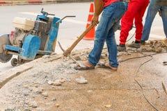 Trabalhador do reparo da perfuração da construção na superfície de estrada com movimento resistente da broca da máquina Imagem de Stock Royalty Free