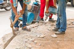Trabalhador do reparo da perfuração da construção na superfície de estrada com movimento resistente da broca da máquina Fotos de Stock Royalty Free