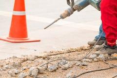 Trabalhador do reparo da perfuração da construção na superfície de estrada com movimento resistente da broca da máquina Imagens de Stock