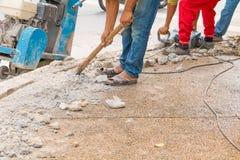 Trabalhador do reparo da perfuração da construção na superfície de estrada com movimento resistente da broca da máquina Foto de Stock Royalty Free