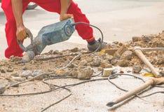 Trabalhador do reparo da perfuração da construção na superfície de estrada com movimento resistente da broca da máquina Imagens de Stock Royalty Free