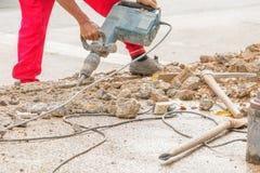 Trabalhador do reparo da perfuração da construção na superfície de estrada com movimento resistente da broca da máquina Imagem de Stock