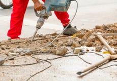 Trabalhador do reparo da perfuração da construção na superfície de estrada com movimento resistente da broca da máquina Fotos de Stock