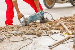Trabalhador do reparo da perfuração da construção na superfície de estrada com movimento resistente da broca da máquina Fotografia de Stock