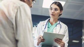 Trabalhador do setor da saúde que toma notas do paciente masculino fotos de stock