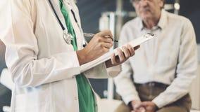 Trabalhador do setor da saúde que toma notas do paciente masculino superior fotografia de stock