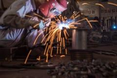 Trabalhador do soldador da indústria pesada na mão da máscara protetora que guarda a tocha de soldadura do arco que trabalha na c imagem de stock