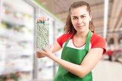 Trabalhador do supermercado que apresenta o saco dos feijões foto de stock royalty free