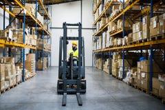Trabalhador do warehouseman com empilhadeira Foto de Stock Royalty Free
