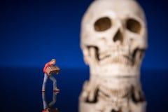 Trabalhador e crânio obscuro com fundo lustroso azul imagens de stock royalty free