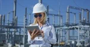 Trabalhador elétrico fêmea de sorriso em uma tabuleta imagem de stock royalty free