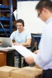 Trabalhador em auriculares do armazém e no portátil vestindo da utilização foto de stock royalty free