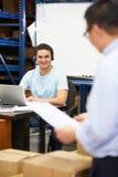 Trabalhador em auriculares do armazém e no portátil vestindo da utilização imagens de stock