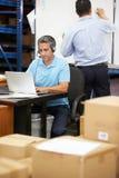 Trabalhador em auriculares do armazém e no portátil vestindo da utilização imagens de stock royalty free
