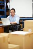 Trabalhador em auriculares do armazém e no portátil vestindo da utilização fotografia de stock