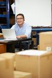 Trabalhador em auriculares do armazém e no portátil vestindo da utilização fotos de stock royalty free