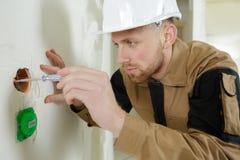 Trabalhador em fios outting do capacete na construção nova foto de stock royalty free