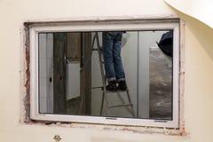 Trabalhador em suportes uniformes na escada portátil na abertura da janela Equipe da construção do conceito, trabalhos de termina imagens de stock