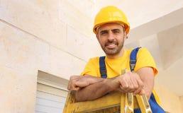 Trabalhador em um capacete de segurança que leva uma escada Imagem de Stock Royalty Free