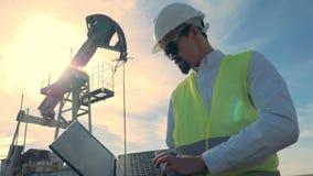 Trabalhador em um fundo do por do sol, fim das bombas de óleo acima filme
