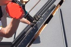 Trabalhador em um telhado com a broca elétrica que instala a telha do metal na casa de madeira Imagem de Stock Royalty Free