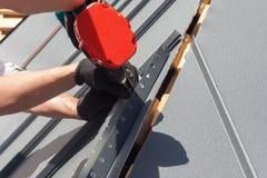 Trabalhador em um telhado com a broca elétrica que instala a telha do metal na casa de madeira Fotografia de Stock Royalty Free
