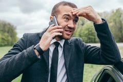 Trabalhador europeu urbano novo considerável que usa o dispositivo móvel fora Empresário de vista na moda que faz a conversação d fotos de stock royalty free