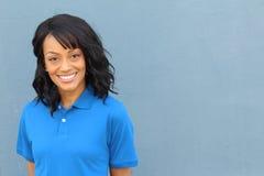 Trabalhador fêmea afro-americano do colarinho azul que levanta no cruzamento uniforme isolado no azul Fotografia de Stock