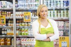 Trabalhador fêmea com os braços cruzados na mercearia imagem de stock royalty free