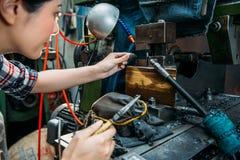 Trabalhador fêmea concentrado do torno que guarda alicates Imagem de Stock