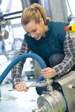 Trabalhador fêmea da cervejaria com maquinaria de engarrafamento na fábrica fotografia de stock royalty free