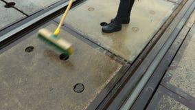 Trabalhador fêmea da estrada de ferro limpo com opinião superior de cruzamento de estrada de ferro da escova filme